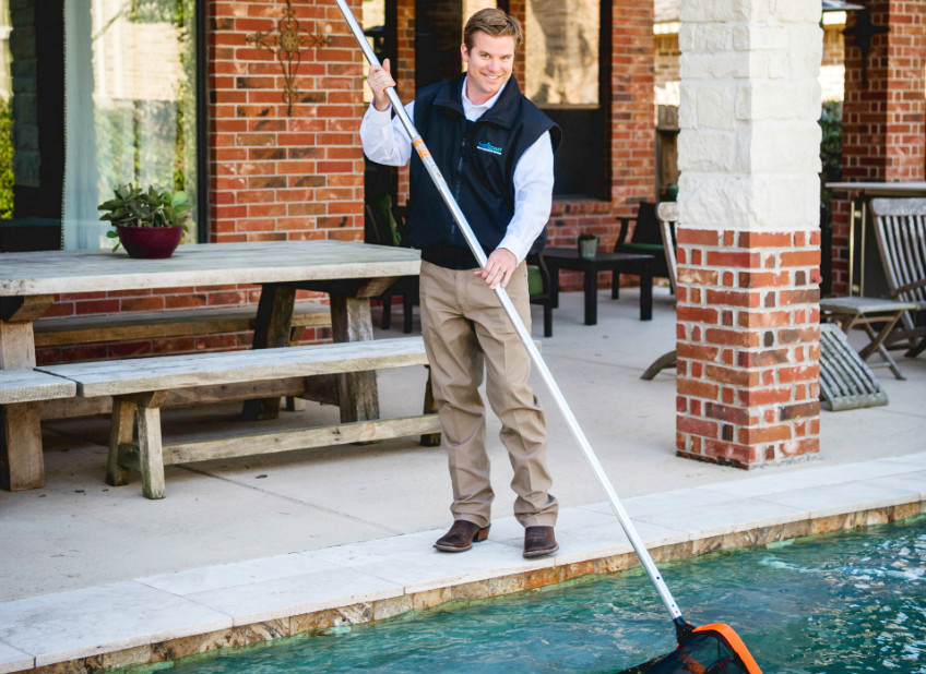Third Coast employee cleaning pool with net.